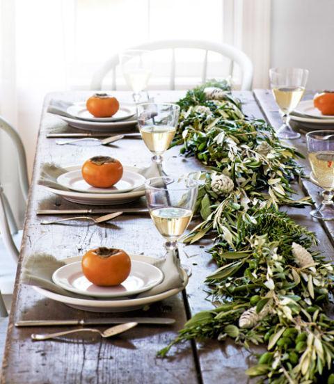 Caquis persimon y ramas adornan esta mesa otoñal.