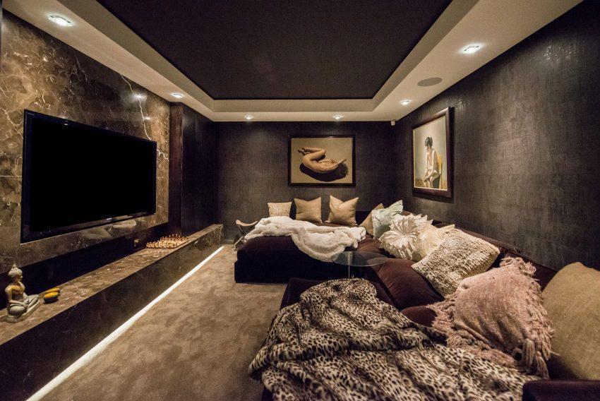 Un gran sofá modular con chaise longues y muchos cojines en la sala de TV.