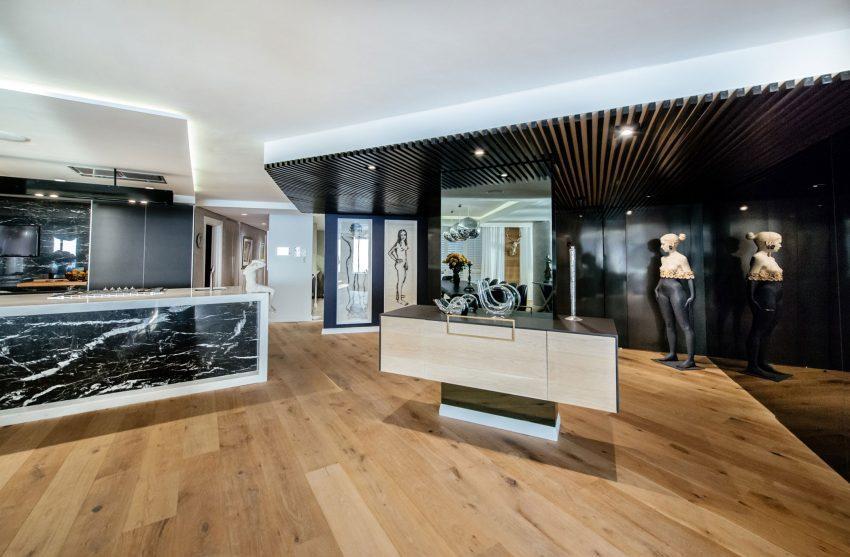 La pared de la sala de estar que da al salón principal, está cubierta de vidrio negro.