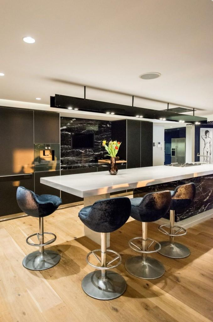 Imagen frontal de la cocina, con una barra de desayuno en primer plano.