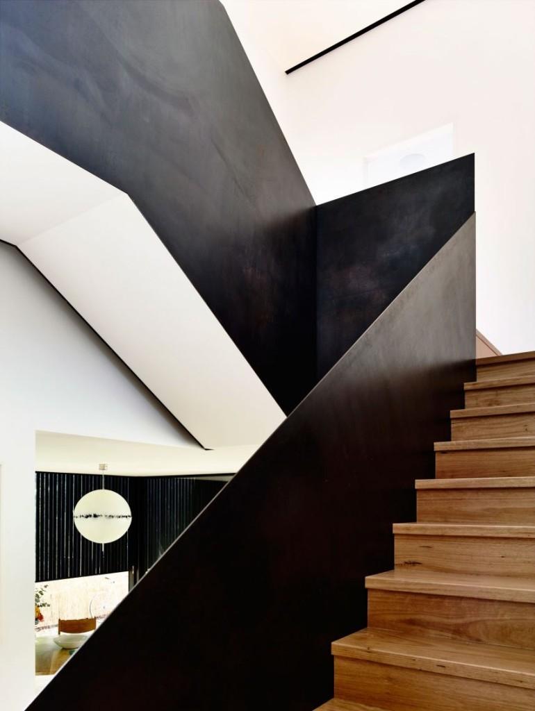 Blanco, negro y madera y metal son los tonos y los materiales de esta escalera.