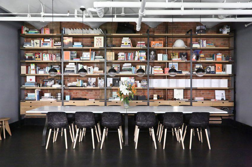 Una gran estantería repleta de libros, ocupa toda una pared en este amplio comedor.