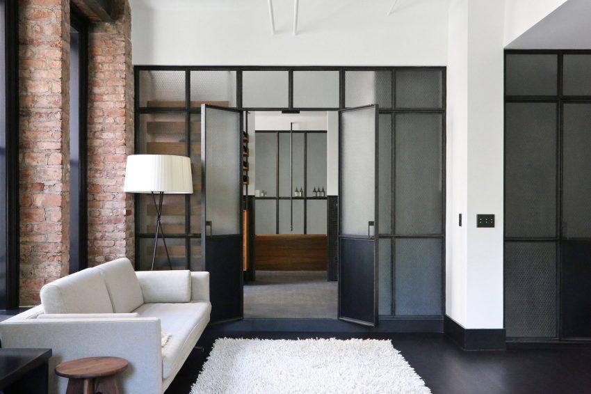 Grandes cerramientos de estilo industrial dan acceso al baño y al vestidor.
