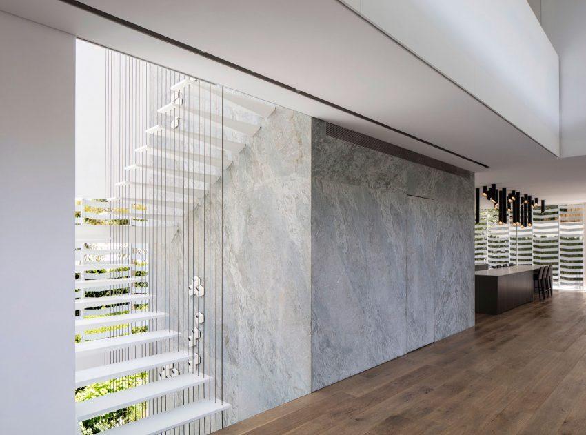 Junto a la escalera paredes panelada con planchas que imitan el mármol.