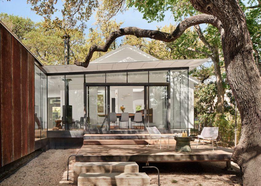 Un espacio transparente tras la antigua casa, de estilo contemporáneo.