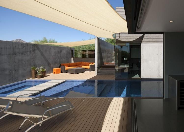 Al otro lado de la piscina un conjunto de sofás modulares, con una tapicería de un vivo tono naranja.