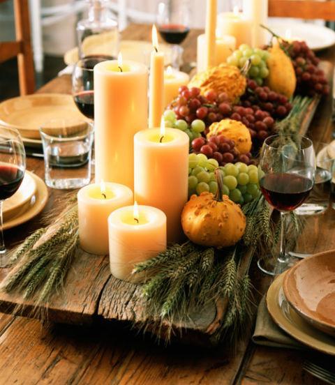 Uvas, espigas, velas y fruta en esta campestre composición.