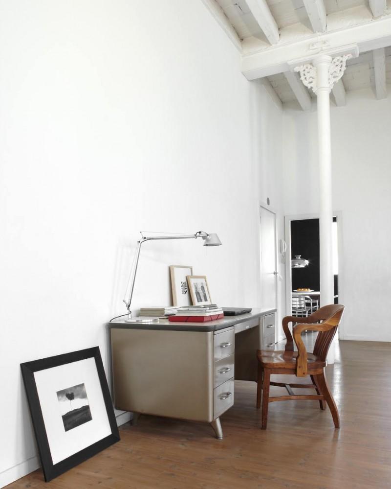 El espacio de trabajo, lo componen un escritorio metálico y un sillón de madera.