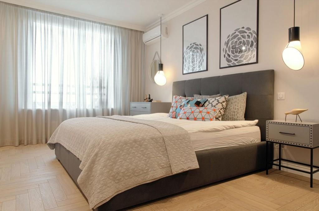 Una cama con base y cabecero tapizados en color gris.