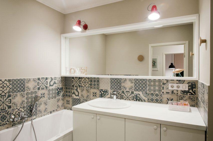 Mobiliario y sanitarios blancos combinados con baldosas hidráulicas.