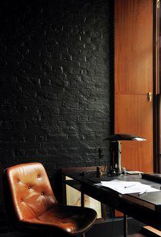 Piel marrón, madera en tono cálido y ladrillo visto pintado de color negro.