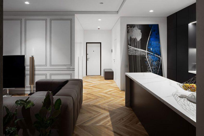 Un diseño de madera dispuesto en espiga cubre el suelo de todo el apartamento.