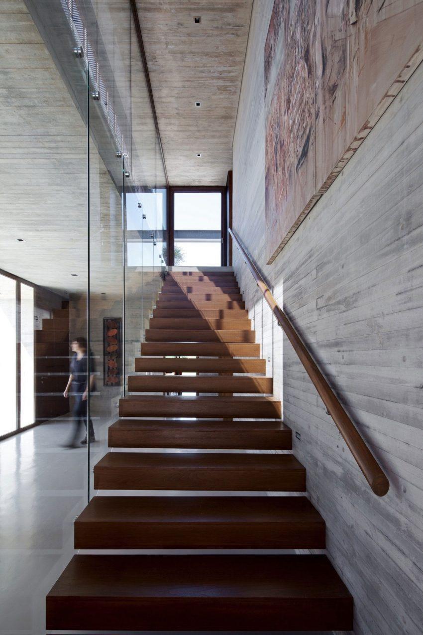 Grandes planchas de grueso cristal y peldaños volados de acero cor-ten, componen la moderna escalera.