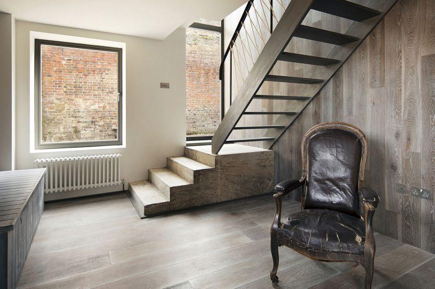 Un sillón clásico con una tapicería de piel muy deteriorada, en un ambiente ecléctico.