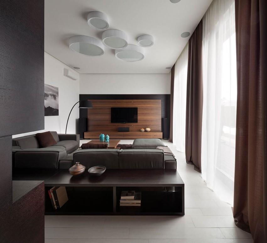 Un salón de estilo contemporáneo, con mobiliario en tonos oscuros.