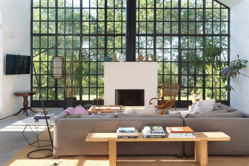 Un par de grandes sofás tapizados en tono gris que, coordinan con el suelo de cemento.