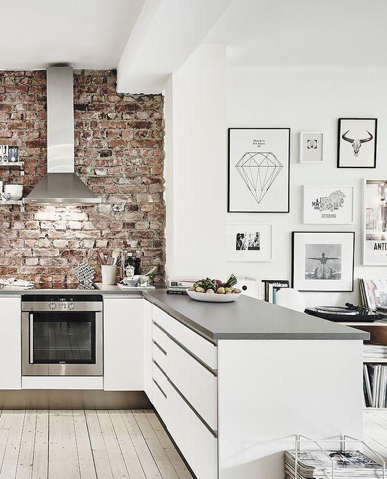 Una cocina con el fuerte contraste del acero inoxidable y el ladrillo visto.