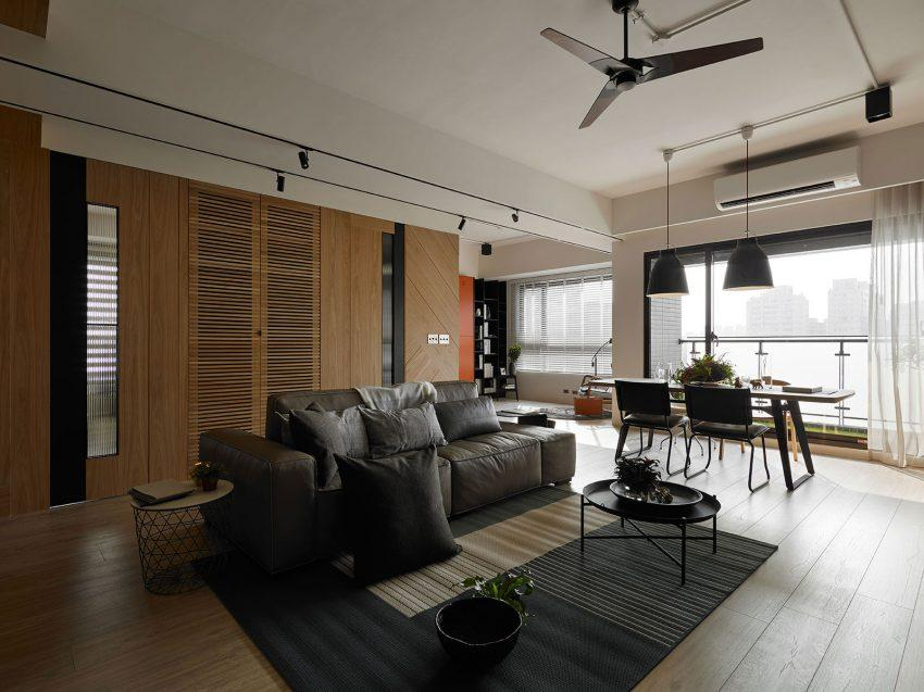 Las puertas y los espacios de almacenaje tras el sofá, juegan con la misma madera.