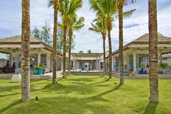 Un elegante camino de palmeras, lleva desde la playa a la vivienda.