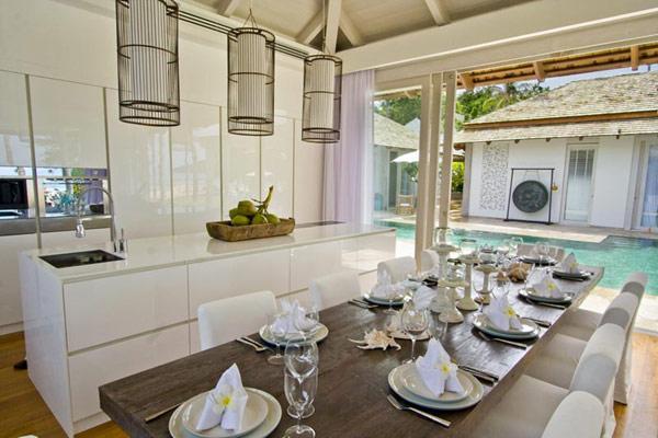 Una mesa de comedor de madera rústica, contrasta con el blanco impoluto del mobiliario de la cocina.