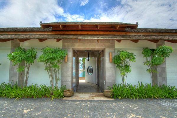 Custodiada por dos parterres con exuberante vegetación, vemos la entrada a esta propiedad.