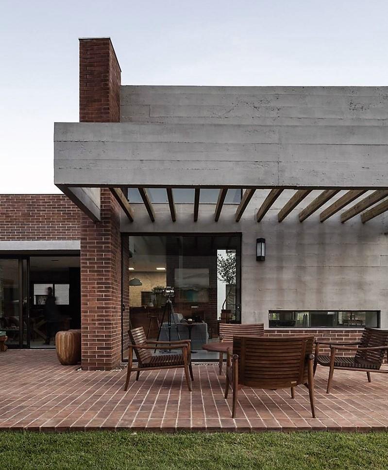 Suelos cubiertos de placas ceramicas, con tono de ladrillo y mobiliario de maderas tropicales para el comedor de exterior.
