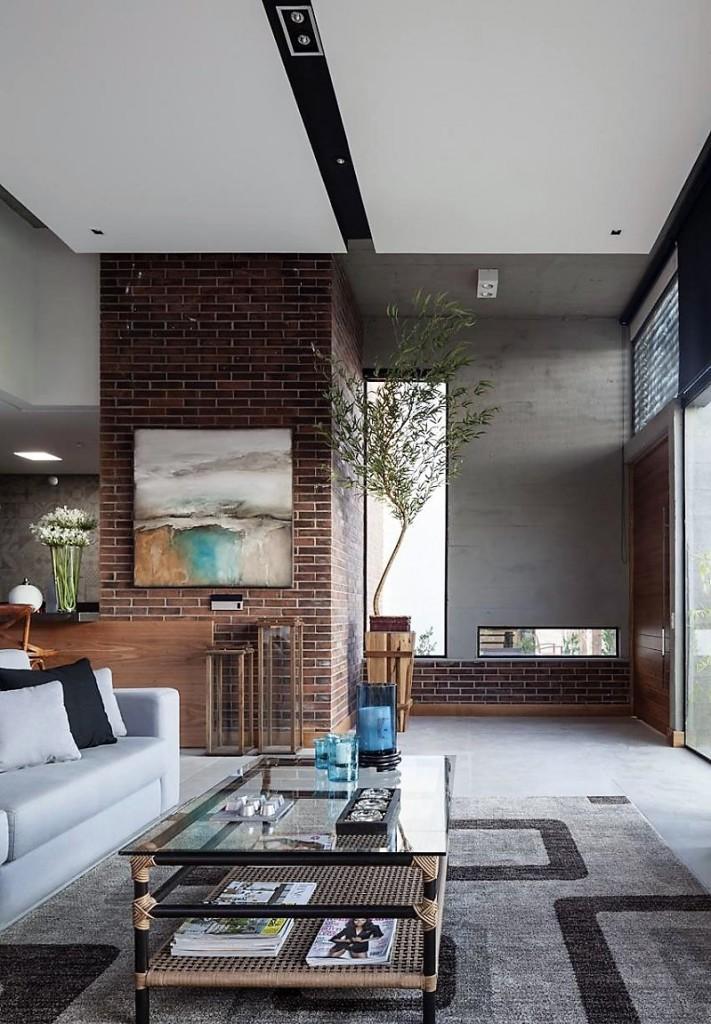 Una imagen general del recibidor y de parte del salón de esta propiedad. En primer plano, una mesa de centro de metal y fibras naturales.