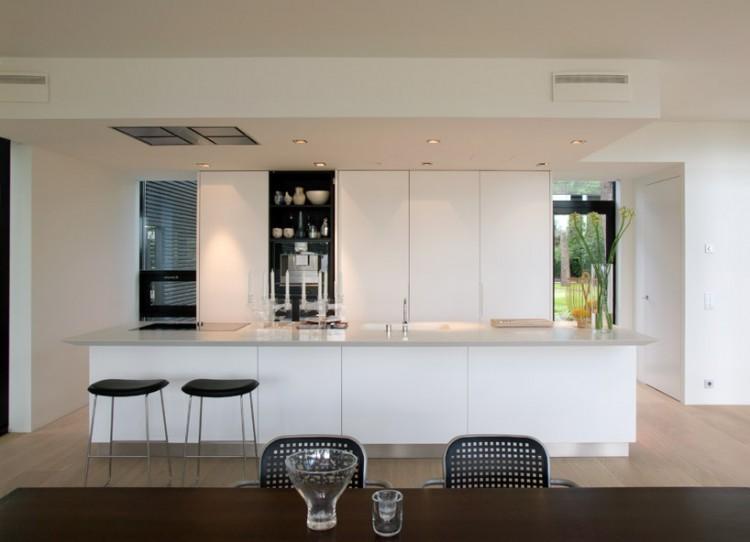 Un par de sencillos taburetes de diseño, en color negro, bajo la barra de desayunos.