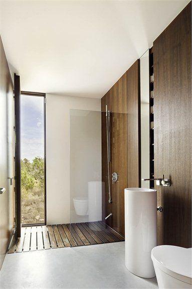 Sanitarios, suelos y techo blancos, combinados con paneles de madera oscura.