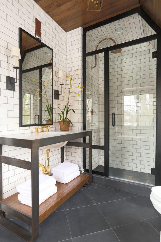 Un cuarto de baño con ducha cerrada, que cuenta con perfileria oscura de aspecto oxidado.