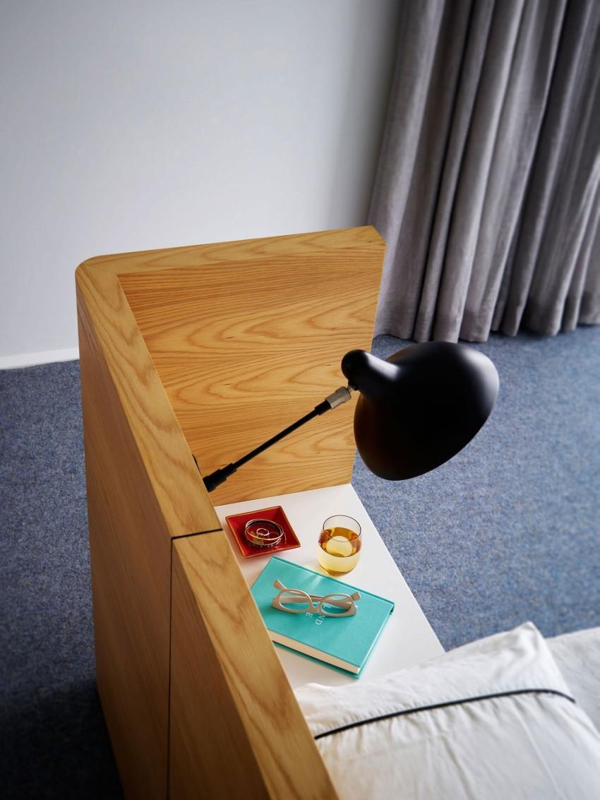 Un cabecero de madera, que cubre la mesillas de noche.