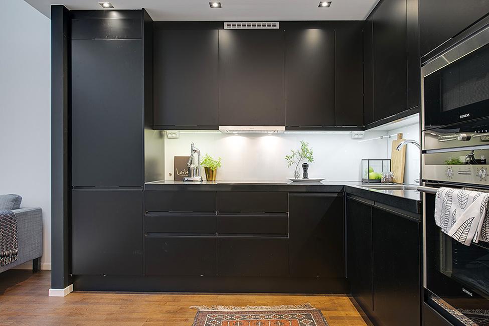 Una moderna cocina de color negro, destaca del resto de la estancia.