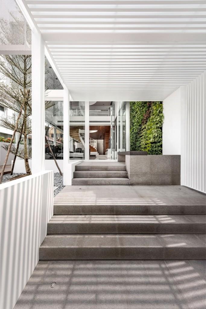 Dos tramos de escalera realizada en hormigón da acceso al interior de la casa.