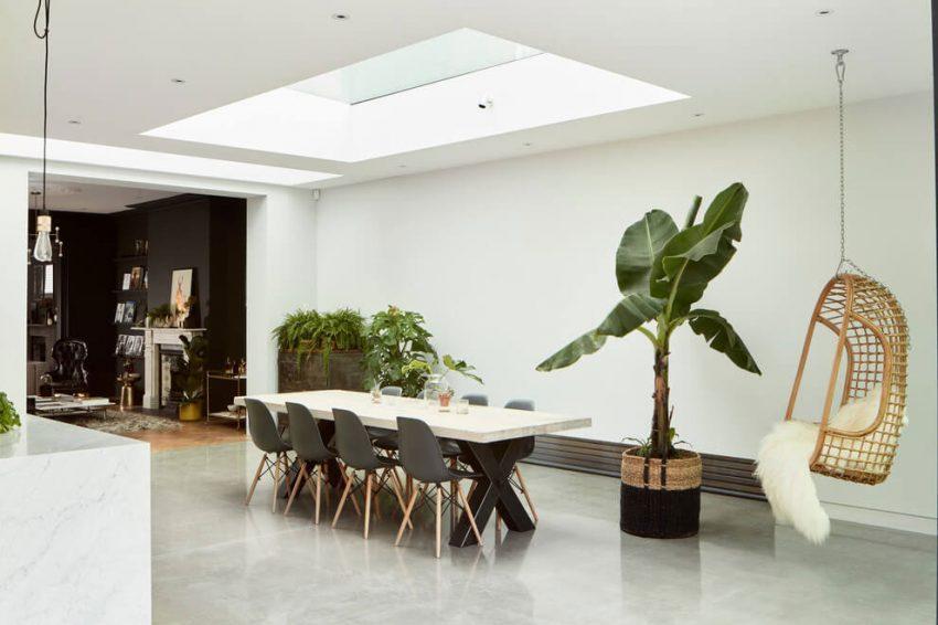 Comedor de paredes blancas y plantas tropicales.