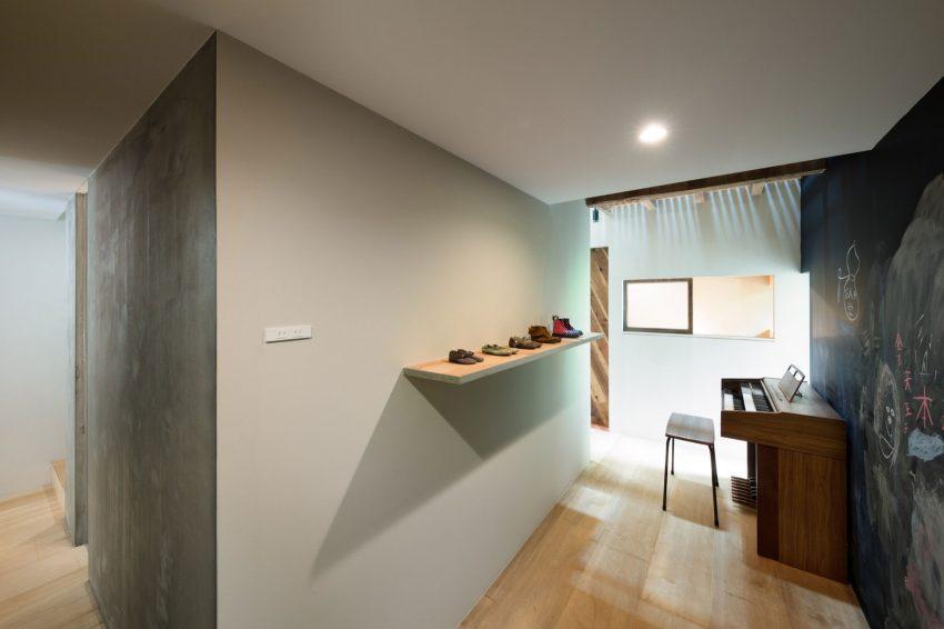 Un rincón con un piano de pared.