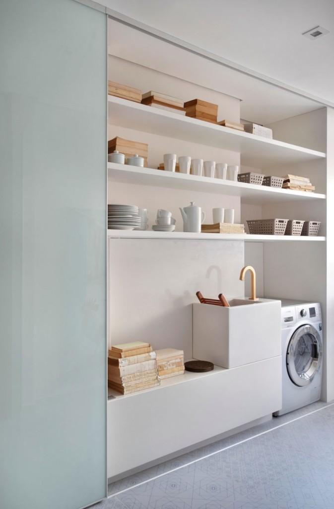 Un espacio de almacenaje, sobre una pequeña pila de lavado y una lavadora.