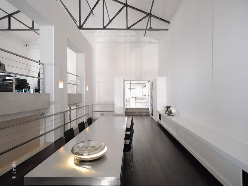 Un minimalista comedor con una mesa de acero inoxidable.