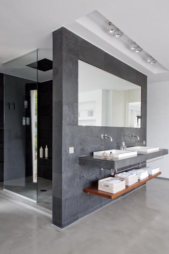 Una gran ducha con una mampara central de cristal.