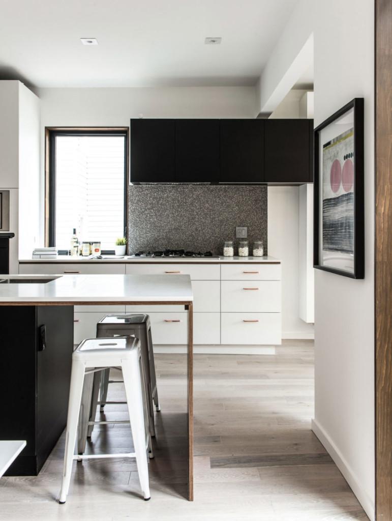 Tonos grises, negros y blancos, se combinan con la madera en el diseño de la cocina.