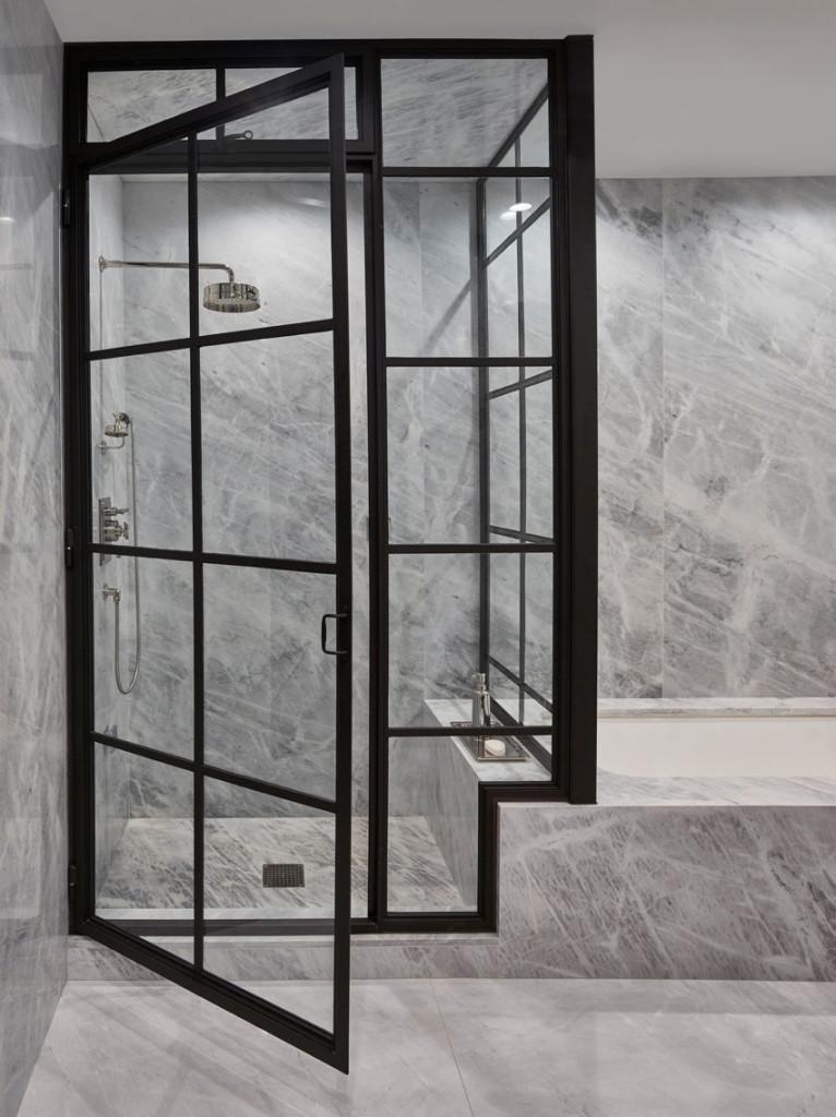 Baño de mármol, con puertas metálicas negras y vidrio transparente.