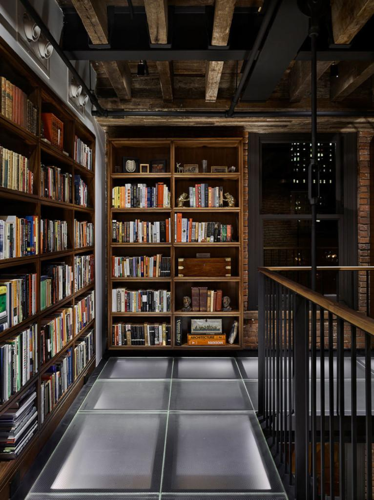 Imagen de la magnífica biblioteca de madera, en la galería que cuenta con un original suelo de cristal translucido.