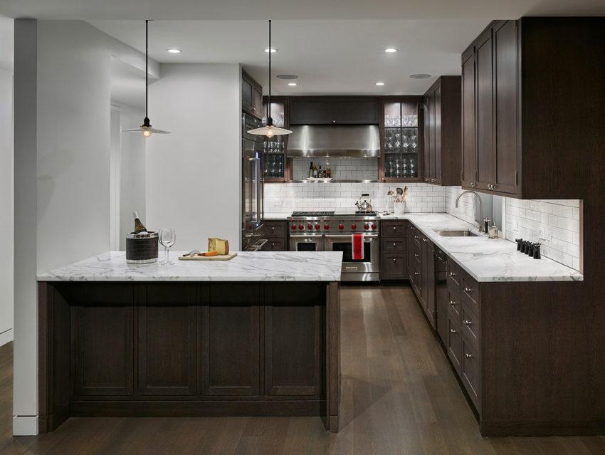 Cocina de madera oscura, con encimeras a contraste de mármol blanco.