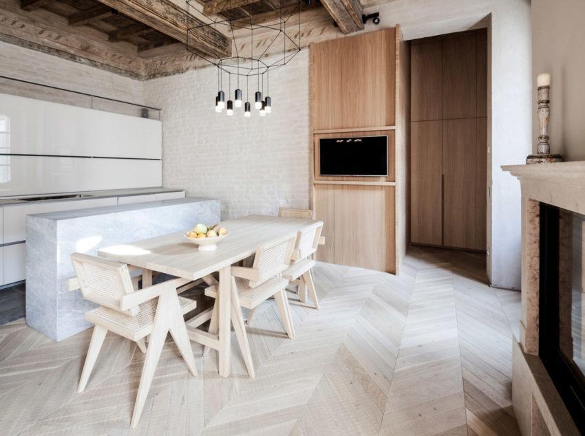 Comedor compuesto de madera clara, con un estilo contemporáneo, combinado con una moderna cocina blanca.