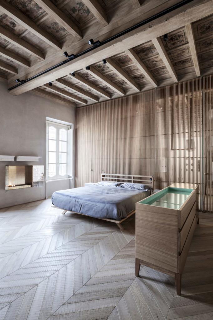Dormitorio con chimenea moderna, junto con suelo y techo de madera de diferentes acabados.