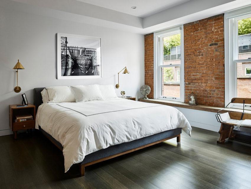 Dormitorio con suelos de madera y pared de ladrillo.