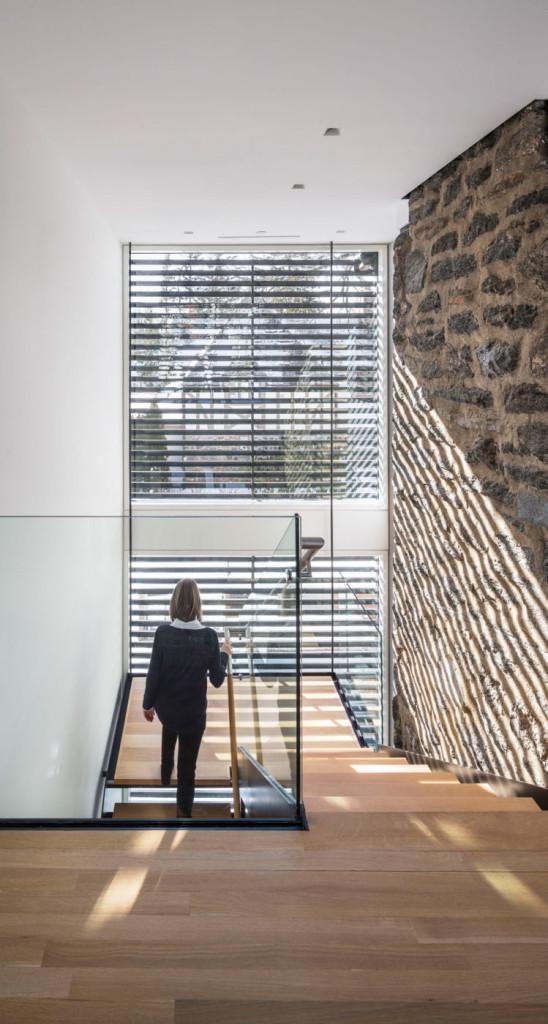 Escaleras de madera , muros de piedra y cristal en el acceso a la planta superior.