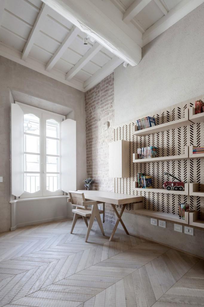 Escritorio compuesto de madera, rodeado de paredes de ladrillo y suelos y techos de madera.
