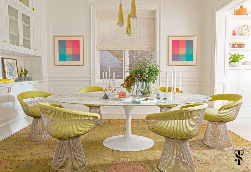 Un moderno comedor, con seis sillones de diseño y una mesa redonda.
