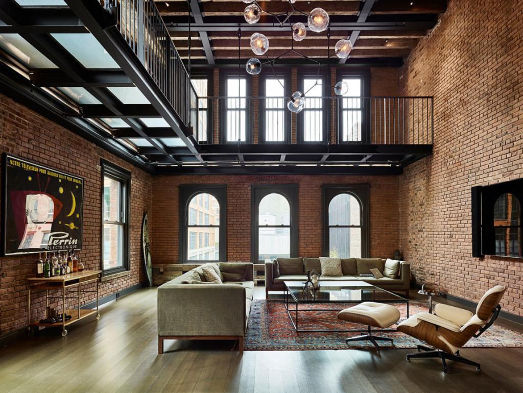 Salón con sofás, mesa de café de cristal y un sillón Eames con otomana blanca, todo enmarcado por paredes de ladrillo visto.