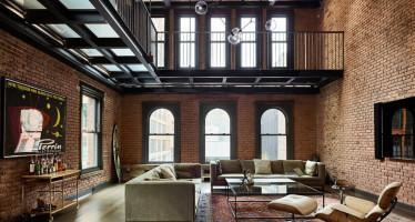 Salón con sofás, mesa de café de cristal y una silla de salón Eames con otomana blanca, todo encerrado por paredes de ladrillo expuestas